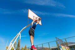 Jugador joven de la calle del baloncesto que hace clavada Fotografía de archivo libre de regalías