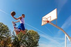 Jugador joven de la calle del baloncesto que hace clavada Imagen de archivo libre de regalías