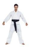 Jugador masculino del karate que presenta en el fondo blanco Foto de archivo