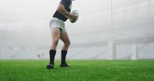 Jugador masculino del rugbi que ata cordones en el estadio 4k almacen de metraje de vídeo