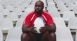 Jugador masculino del rugbi que se sienta con la bola de rugbi en el estadio 4k metrajes