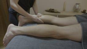 Jugador masculino profesional atlético del deporte que recibe un masaje de los becerros de un masajista experimentado en un centr almacen de metraje de vídeo