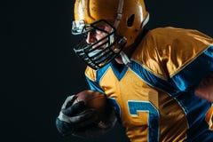 Jugador ofensivo del fútbol americano con la bola imagen de archivo libre de regalías