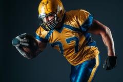 Jugador ofensivo del fútbol americano con la bola imagenes de archivo