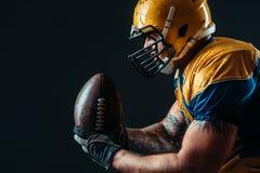 Jugador ofensivo del fútbol americano con la bola foto de archivo libre de regalías