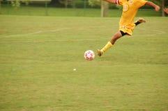 Jugador que golpea la bola con el pie Foto de archivo libre de regalías