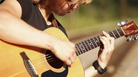 Jugador rubio de pelo largo de la guitarra acústica almacen de metraje de vídeo