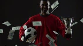Jugador talentoso del deporte que celebra el éxito, billetes de dólar que caen abajo, carrera almacen de video