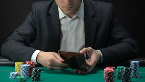 Jugador trastornado que mira en cartera vacía, perdedor en la tabla del casino, apego del juego almacen de metraje de vídeo