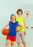 Jugadores de básquet felices que presentan con la bola en gimnasio Fotografía de archivo
