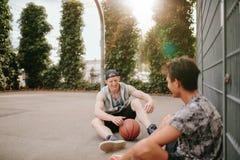 Jugadores de básquet jovenes que se sientan en corte y la sonrisa Foto de archivo libre de regalías