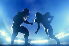 Jugadores de fútbol americano en el juego, funcionamiento del estratega Luces del estadio imagen de archivo