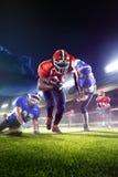 Jugadores de fútbol americano en la acción en arena magnífica Fotografía de archivo libre de regalías