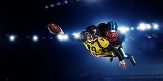 Jugadores de fútbol americano en la arena Técnicas mixtas imágenes de archivo libres de regalías
