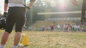 Jugadores de fútbol americano que luchan para la bola en el campo, ocio activo para los hombres metrajes