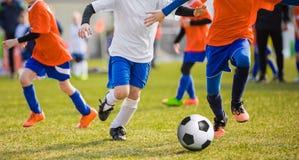 Jugadores de fútbol corrientes del fútbol de los niños con la bola Futbolistas que golpean el juego con el pie Fotos de archivo