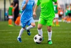 Jugadores de fútbol de la juventud Muchachos que golpean la bola del fútbol con el pie en el campo Foto de archivo libre de regalías