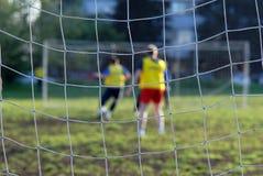 Jugadores de fútbol delante de la red imagen de archivo