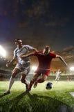 Jugadores de fútbol en la acción en fondo del estadio de la puesta del sol Imagen de archivo libre de regalías