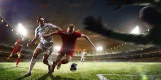 Jugadores de fútbol en la acción en panorama del fondo del estadio de la puesta del sol