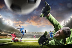 Jugadores de fútbol en la acción en panorama del fondo del estadio de la puesta del sol Imagen de archivo libre de regalías