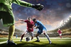 Jugadores de fútbol en la acción en panorama del fondo del estadio de la puesta del sol Imagenes de archivo