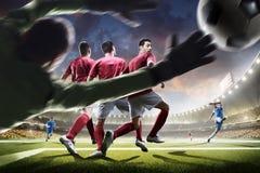 Jugadores de fútbol en la acción en panorama del fondo del estadio de la puesta del sol Foto de archivo