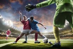 Jugadores de fútbol en la acción en panorama del fondo del estadio de la puesta del sol Imagen de archivo