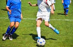 Jugadores de fútbol jovenes con una bola Imagen de archivo libre de regalías