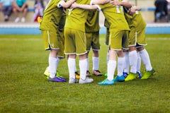 Jugadores de fútbol jovenes del fútbol en ropa de deportes amarilla El joven se divierte al equipo de fútbol Fotos de archivo