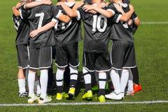 Jugadores de fútbol jovenes del fútbol en ropa de deportes negra El joven se divierte al equipo de fútbol Fotografía de archivo