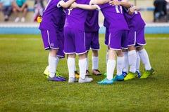 Jugadores de fútbol jovenes del fútbol en ropa de deportes púrpura El joven se divierte al equipo de fútbol Imagenes de archivo