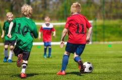 Jugadores de fútbol jovenes del fútbol que corren y que golpean la bola con el pie en deportes Foto de archivo