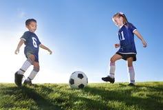 Jugadores de fútbol jovenes que golpean la bola con el pie Fotos de archivo libres de regalías