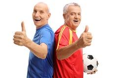 Jugadores de fútbol mayores alegres que detienen sus pulgares Fotografía de archivo libre de regalías