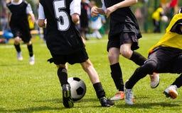 Jugadores de fútbol que compiten para la bola Partido de fútbol de la escuela primaria Imagenes de archivo