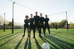 Jugadores de fútbol que se unen en echada Imagenes de archivo
