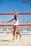 Jugadores de las mujeres del voleibol de playa salto Imagenes de archivo