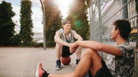 Jugadores de Streetball que toman resto después de jugar a un juego Foto de archivo libre de regalías