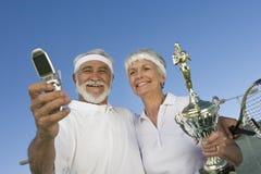 Jugadores de tenis con el trofeo que toma el autorretrato Fotos de archivo