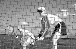Jugadores de tenis de la mujer que miran la cámara a través de la red que espera para jugar mientras que mira la cámara Foto de archivo