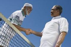 Jugadores de tenis de sexo masculino mayores que sacuden las manos fotografía de archivo
