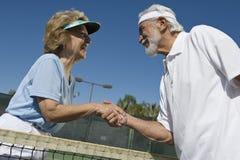 Jugadores de tenis mayores activos que sacuden las manos Foto de archivo libre de regalías