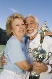 Jugadores de tenis mayores con el abarcamiento del trofeo Imagen de archivo libre de regalías
