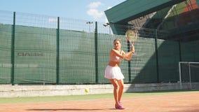 Jugadores de tenis que juegan un partido en la corte en un día soleado almacen de metraje de vídeo