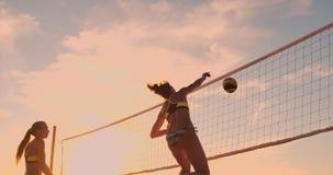 Jugadores de voleibol femeninos jovenes pasar y clavar la bola sobre la red en una tarde soleada del verano Muchachas caucásicas  almacen de metraje de vídeo