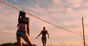 Jugadores de voleibol femeninos jovenes pasar y clavar la bola sobre la red en una tarde soleada del verano Muchachas caucásicas  almacen de video