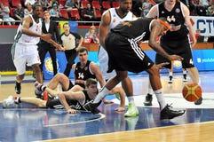 Jugadores en el piso después de la lucha para la bola Imágenes de archivo libres de regalías