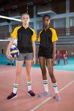 Jugadores femeninos que se colocan así como bola en la corte de voleibol Fotografía de archivo