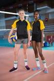 Jugadores femeninos que se colocan así como bola en la corte de voleibol Imagen de archivo